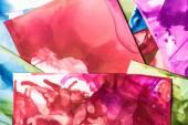 Fotografie červené, fialové a zelené stříkance barev alkoholu jako abstraktní pozadí