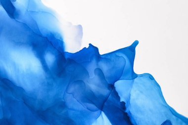 blue splashes of alcohol ink on white as abstract background