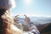 Fotografie oříznuté záběr ženy pořízení fotografie hory s smartphone, Karpaty, Ukrajina