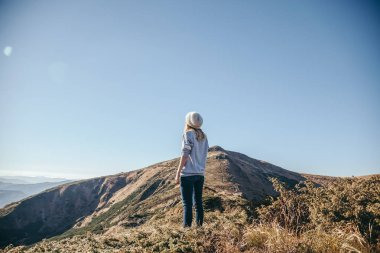 rear view of woman looking at mountains on sunny day, Carpathians, Ukraine