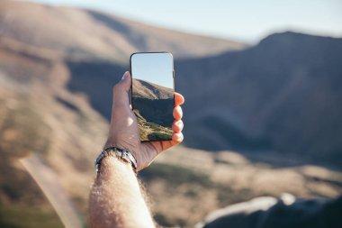 cropped shot of man taking photo of mountain with smartphone, Carpathians, Ukraine