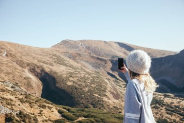 rear view of woman taking photo of mountain with smartphone with blank screen, Carpathians, Ukraine