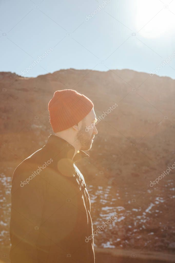 handsome young man in red hat looking away in front of mountain on sunny day, Carpathians, Ukraine