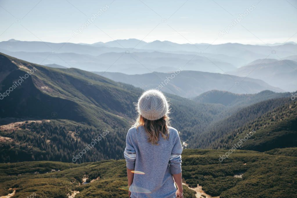 rear view of female traveler looking at scenic mountains on sunny day, Carpathians, Ukraine