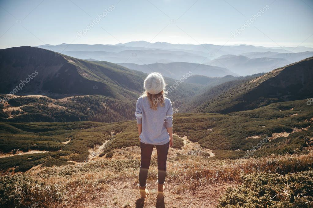 back view of female traveler looking at beautiful mountains on sunny day, Carpathians, Ukraine