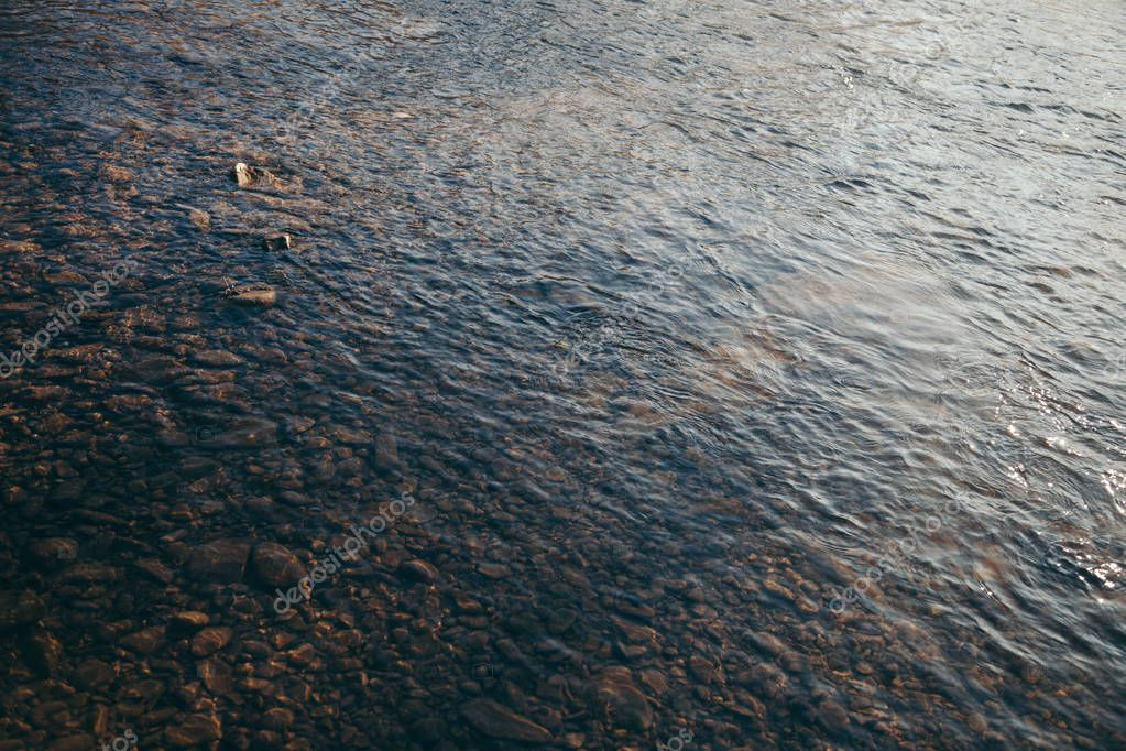 close-up shot of beautiful transparent water over pebbles in mountain river, Carpathians, Ukraine