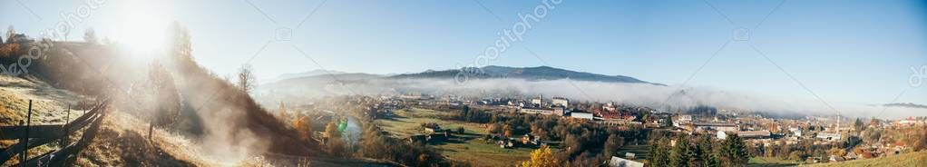 Panoramic view of beautiful mountains and Vorokhta town under blue sky, Carpathians, Ukraine