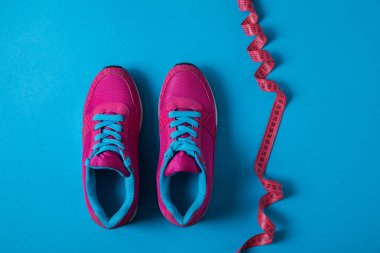 View from above of pink sport shoes and measuring tape isolated on blue, minimalistic concept stock vector