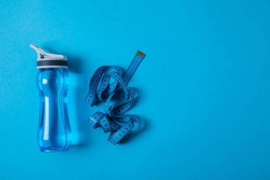 top view of sport bottle and measuring tape isolated on blue, minimalistic concept