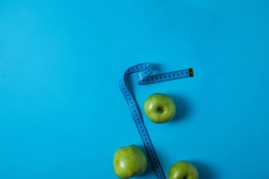 top view of delicious green apples and measuring tape isolated on blue