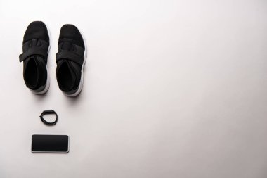 view from above of arranged black sport shoes, fitness tracker and smartphone with blank screen isolated on white