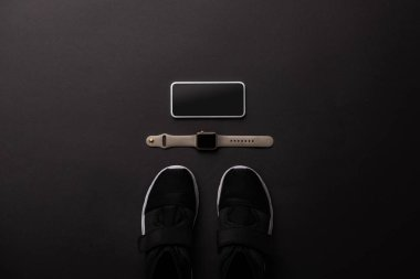 flat lay with arranged smartphone, smartwatch and sneakers isolated on black, minimalistic concept