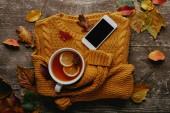 flache Liege mit Tasse Tee, Schmuckpullover, Smartphone mit leerem Bildschirm und abgefallenen Blättern auf Holzoberfläche