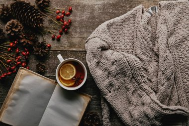 flat lay with red holly berries, blank notebook, cup of tea and knitted sweater on wooden tabletop