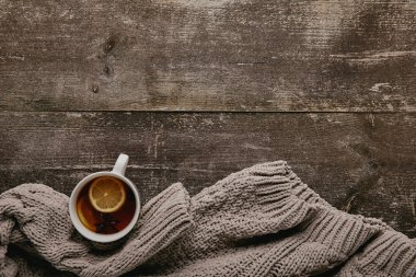 flat lay with grey sweater and cup of tea with lemon pieces on wooden tabletop