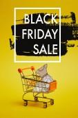 zblízka pohled malý nákupní vozík s papírové oblečení na žluté pozadí, černý pátek prodej nápis