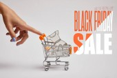 Fotografie cropped shot of female hand and little shopping cart with paper clothes on grey background, black friday sale inscription