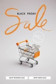 Fotografie close up view of shopping cart with little goods made of paper on grey background, black friday sale inscription