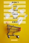 Fényképek felülnézet kis bevásárló kocsi papír ruhát a sárga hátteret, ne hagyd, hogy ez eladó csúszik el a felirat