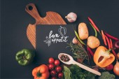 Photo top view of black board on wooden table with vegetables on gray table, bon appetit lettering