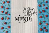 pohled na ubrousek a cherry rajčata s rukolou na modrém stole, shora nápis menu