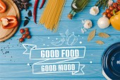 top view of ingredients for cooking pasta on blue table, good food good mood lettering