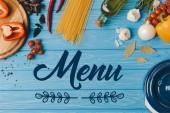 pohled z přísad pro vaření těstovin na modrém stole, shora nápis menu