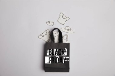 top view of black shopping bag with black friday inscription and paper clothes on grey background
