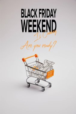 close up view of shopping cart with little goods made of paper on grey background, black friday weekend inscription