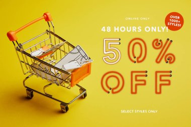 close up view of little shopping trolley with paper clothes on yellow backdrop, discount banner concept