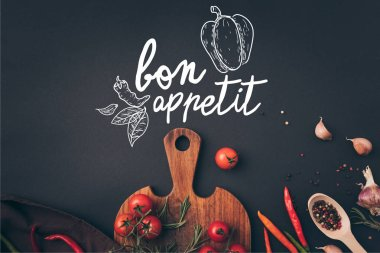 top view of cherry tomatoes and fennel with garlic on gray table with bon appetit lettering