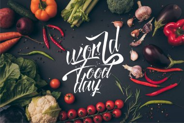 top view of unprocessed vegetables on gray table with world food day lettering