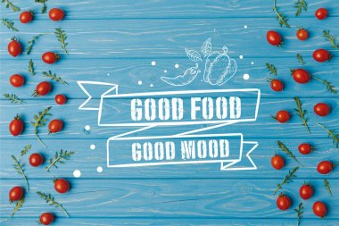 top view of cherry tomatoes with arugula on blue table, good food good mood lettering