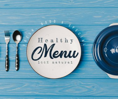 top view of fork, spoon and plates on blue table, healthy menu lettering