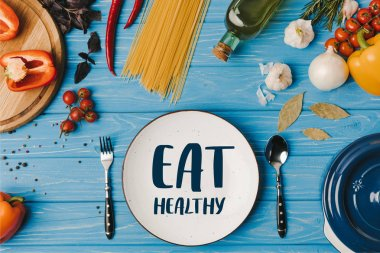 top view of ingredients for cooking pasta on blue table, eat healthy lettering