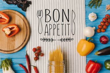 top view of uncooked pasta and ripe vegetables on napkin on blue table, bon appetit lettering
