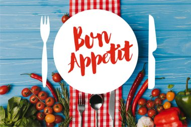 top view of pan and unprocessed vegetables on blue table, bon appetit lettering
