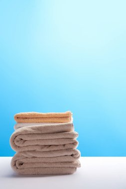 Stack of clean fresh towels on white table on blue background stock vector