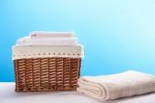 Fotografie Koš na prádlo a čisté měkké ručníky na modré