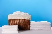 kiadványról laundry basket és a tiszta, puha fehér törölközőt a kék