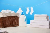 Koš na prádlo, plastové kontejnery s prací kapaliny, hromadu čisté měkké ručníky a bílé ponožky visí na laně na modré