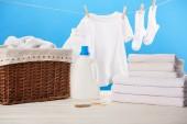 Fotografie Plastikbehälter mit Waschflüssigkeiten, Wäschekorb, Handtüchern und sauberer weißer Kleidung auf blauem Grund