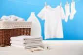 Wäschekorb, Plastikbehälter mit Waschflüssigkeit, Stapel sauberer weicher Handtücher und weiße Kleidung, die an einer Wäscheleine auf blauem Grund hängt