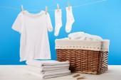 Fotografie Wäschekorb, Stapel sauberer weicher Handtücher und weiße Kleidung, die an der Wäscheleine auf blauem Grund hängt