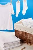 Detailní pohled na koš na prádlo, hromadu čisté měkké ručníky a bílé šaty visí na prádelní šňůru na modré