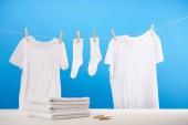 Fotografie Stapel auf saubere Handtücher, Wäscheklammern und weiße Kleider hängen am Seil auf blau