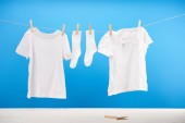 clean white socks and t-shirts hanging on clothesline on blue