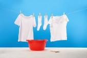 rotes Becken, Wäscheklammern und saubere weiße Kleidung hängen an Seilen auf blauem Grund