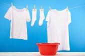 Fotografie rotes Becken und sauberen weißen Klamotten auf der Wäscheleine auf blau