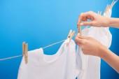Fotografie zugeschnittenen Schuss Person hängen saubere Kleidung mit Wäscheklammern auf der Wäscheleine isoliert auf blau